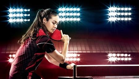 tennis racket: Retrato de mujer joven que juega a tenis en el fondo Negro con luces