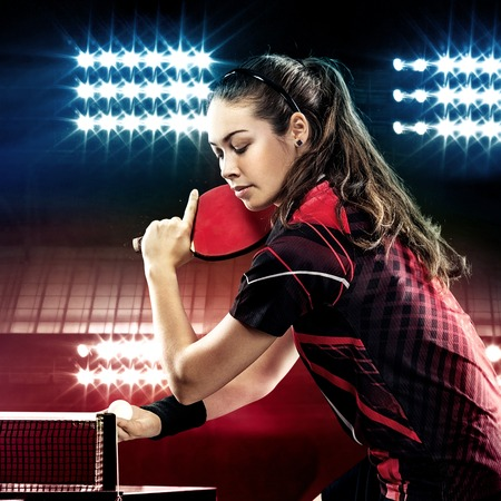 Young pretty sporty girl playing table tennis on black background with lights