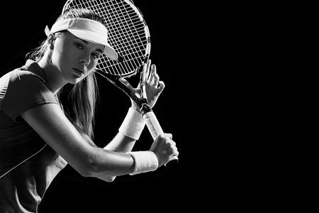 라켓을 가진 아름 다운 여자 테니스 선수의 초상화는 검은 배경에 고립