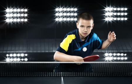 table tennis: Portrait Of Kid Playing Tennis On Black Background Stock Photo