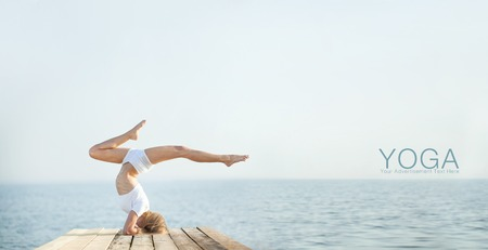 Beautiful blond woman practicing yoga at seashore and meditating