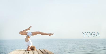 Beautiful blond woman practicing yoga at seashore and meditating