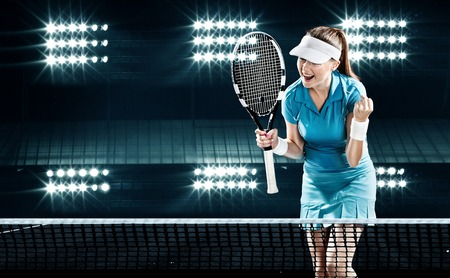 Beautiful girl tennis player with a racket on dark background wiht lights celebrating flawless victory