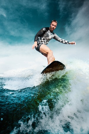 Surfing at blue sea. Young man balanced on wave on surfboard.  Wake surf outdoor lifestyle.