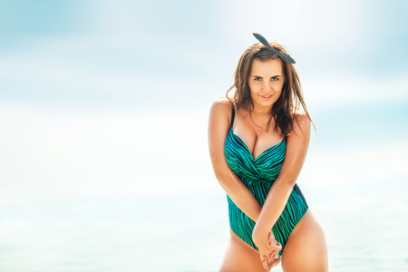 buxom: Woman in swimwear at the sea. Overweight young woman in swimsuit against the sea.