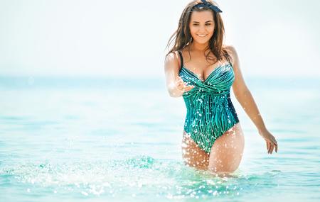 Frau in Badebekleidung am Meer. Übergewichtige junge Frau im Badeanzug gegen das Meer.