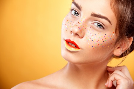 skin art: Youth women with glitter freckles on face, yellow background. Perfect skin. Art concept
