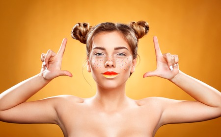 skin art: Youth women with glitter freckles on face happy and smiled on yellow background. Perfect skin. Art concept Stock Photo