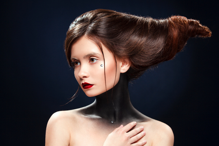 Beautiful girl with a haird in the form of horns. Ads for hairdressers.