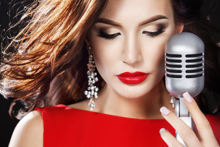 Glamor fashion Woman in red dress with Microphone sing in karaoke at the night club.
