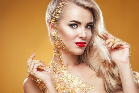 Pretty woman with golden nails and beautiful gold jewelry on yellow background