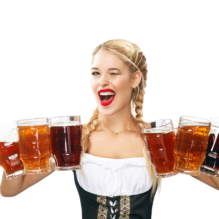 Half-length portrait of young sexy blonde with big breast wearing black dirndl with white blouse holding the beer mug Isolated on dark background Foto de archivo