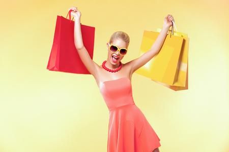 幸せな若い女性が黒い金曜日の休日のショッピングします。黄色の背景に多くの色のバッグを持つ少女。
