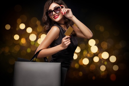 Beautiful young woman make shopping in black friday holiday. Girl with black bag on background with christmas lights. Standard-Bild