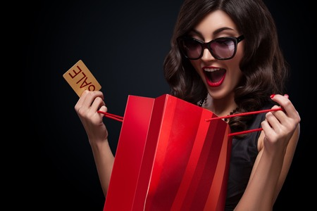 Beautiful young woman make shopping in black friday holiday. Girl with red bag on dark background. Stockfoto