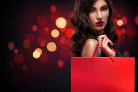Beautiful young woman make shopping in black friday holiday. Girl with red bag on background with christmas lights.