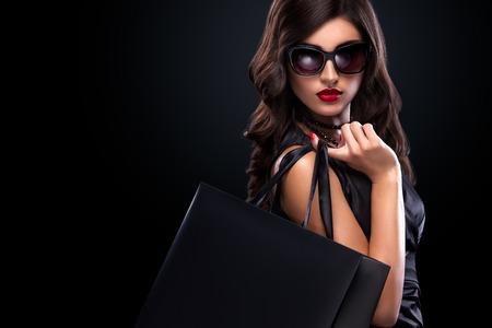 아름 다운 젊은 여자 검은 금요일 휴일에 쇼핑을 확인합니다. 어두운 배경에 검은 가방 소녀입니다.