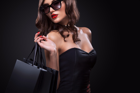 Beautiful young woman make shopping in black friday holiday. Girl with black bag on dark background.