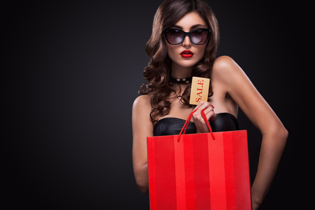 Beautiful young woman make shopping in black friday holiday. Girl with black bag on dark background. Imagens - 66011925