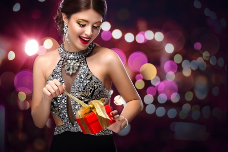 New Year. Young happy woman with gift on bokeh background. Christmas concept.