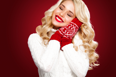 Young happy woman in christmas wear red background. New year concept.