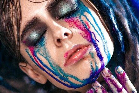 painted face: Portrait of a woman with painted face. Creative makeup and bright style.