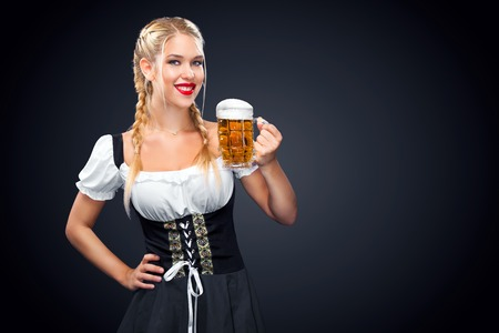 Junge sexy Oktoberfest Kellnerin, ein traditionelles bayerisches Kleid trägt, große Bierbecher auf schwarzem Hintergrund zu dienen. Standard-Bild
