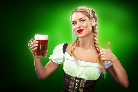 st german: St Patricks Day. Young sexy Oktoberfest waitress, wearing a traditional Bavarian dress, serving big beer mugs on blue background with copy space