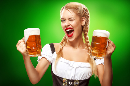 St Patricks Day. Young sexy Oktoberfest waitress, wearing a traditional Bavarian dress, serving big beer mugs on blue background with copy space
