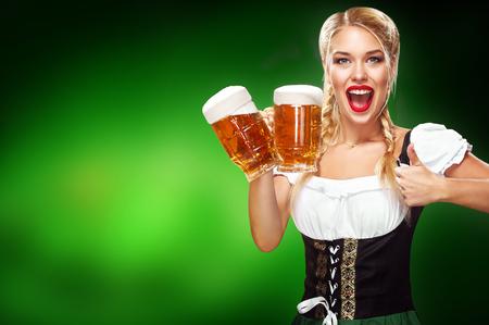 Dia de São Patricio. Jovem garçonete Oktoberfest sexy, vestindo um vestido tradicional da Baviera, servindo canecas de cerveja grande sobre fundo azul, com espaço de cópia