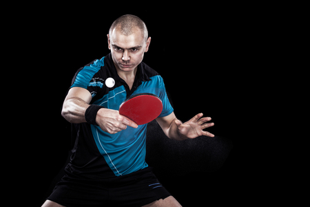 Young sports man tennis-player in play on black background. Action shot. Foto de archivo