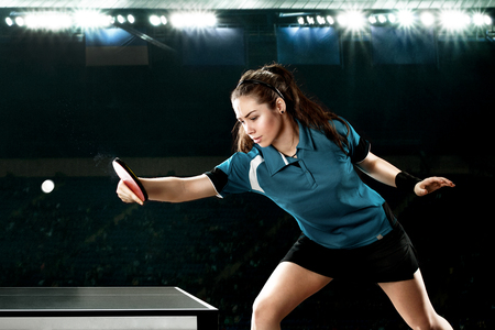 Young handsome woman tennis-player in play on black background. Action shot.