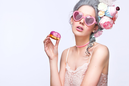 Beautiful blonde woman with a cake. Sweet sexy lady with heart glasses. Vintage style. Fashion photo
