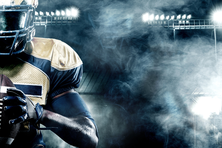 Joueur de sportif football américain sur le stade avec des lumières sur fond avec espace copie