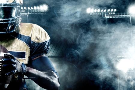 Amerikaanse voetbalsportman speler op stadion met lichten op achtergrond met exemplaarruimte Stockfoto