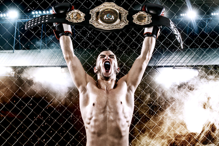 Boxer with Champion belt celebrating flawless victory in boxing cage. Background with lights and smoke. Copy Space. Sport concept.