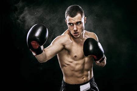 Sportman muay thai bokser vechten in handschoenen in boks kooi. Geïsoleerd op zwarte achtergrond met rook. Ruimte kopiëren.