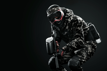 army face: Heavily armed masked paintball soldier isolated on black background. Ad concept.