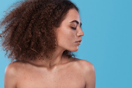 Beauty portrait of girl with afro hairstyle. Girl posing on blue background. Studio shot.