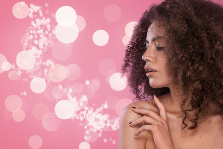 Beauty portrait of girl with afro hairstyle. Girl posing on pink background. Studio shot.