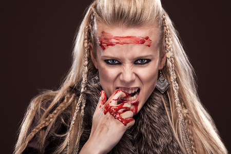 Viking woman in a traditional warrior clothes with blood on face. Stock Photo