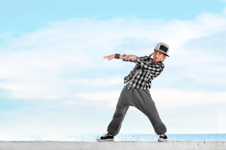 Happy little girl dancing hip-hop on blue sky background