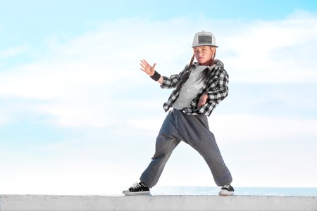 青い空を背景に、ヒップホップを踊る幸せな少女