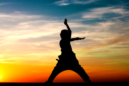 Silhouette of happy little girl dancing on sunset sky background. Yoga. Copy space.