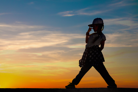 Silhouette of little girl dancing on sunset sky background