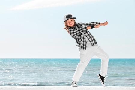 Happy little girl dance on sky background. Fashion kid. Copy space. Stockfoto
