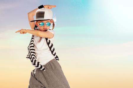 Happy little girl dance on sky background. Fashion kid. Copy space. Archivio Fotografico