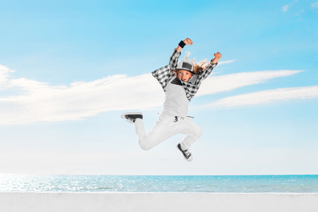 하늘 배경 위에 점프하는 패션 아이. 스톡 콘텐츠