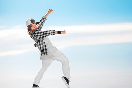 Fashion child dancing over sky background. Stockfoto