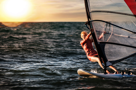 Windsurfing, Fun in the ocean, Extreme Sport. Woman lifestyle